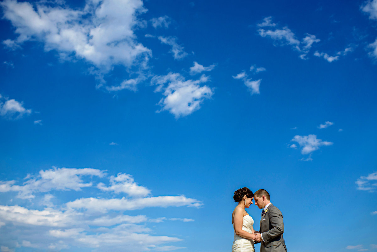 A bride and groom soak in the sun and a blue sky full out fluffy clouds.