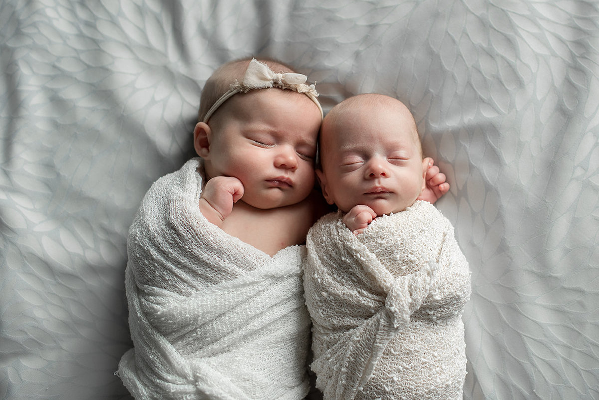 newborn twins cuddled on the bed