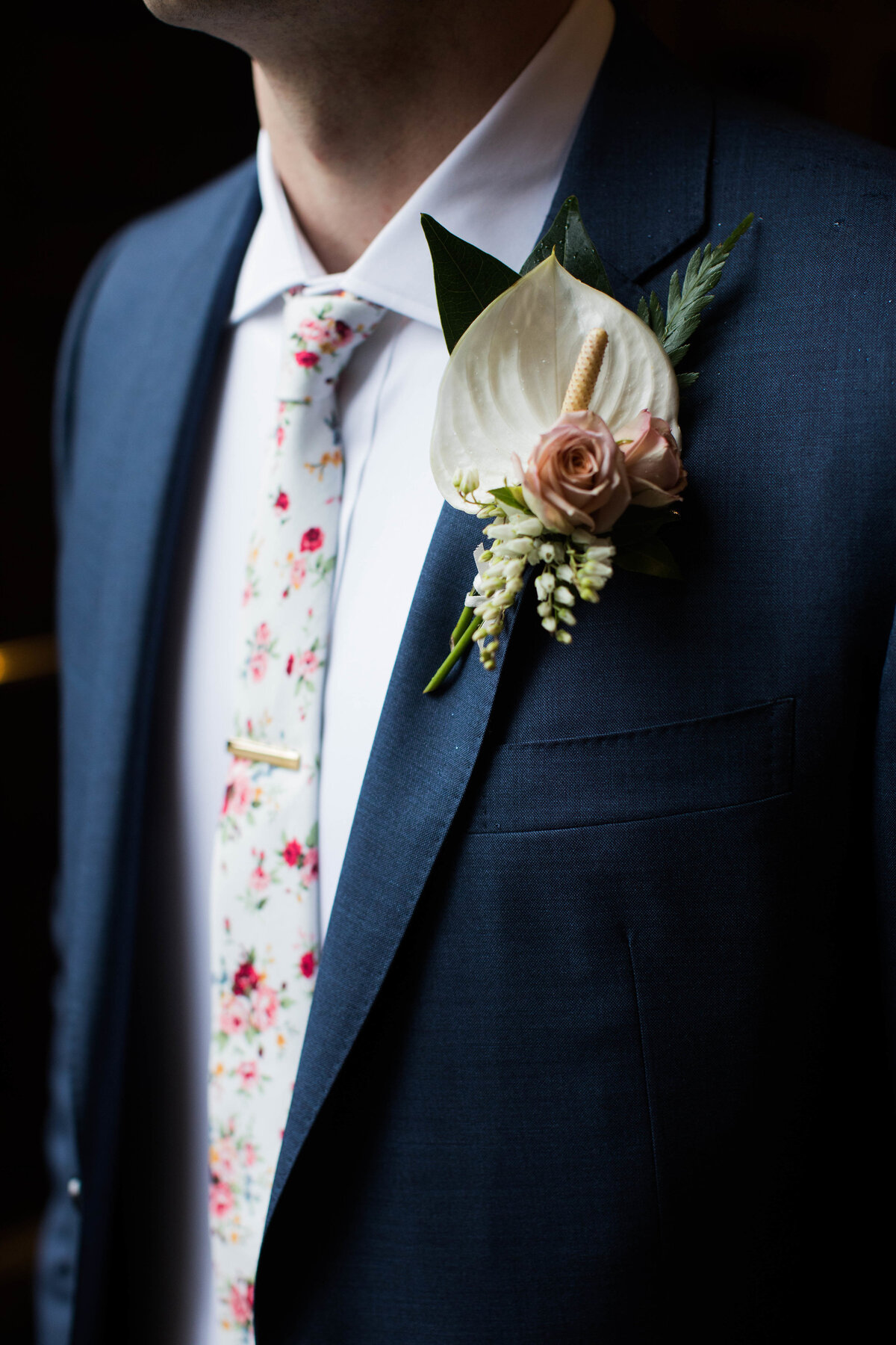 Groom in navy suit with floral tie and boutonniere