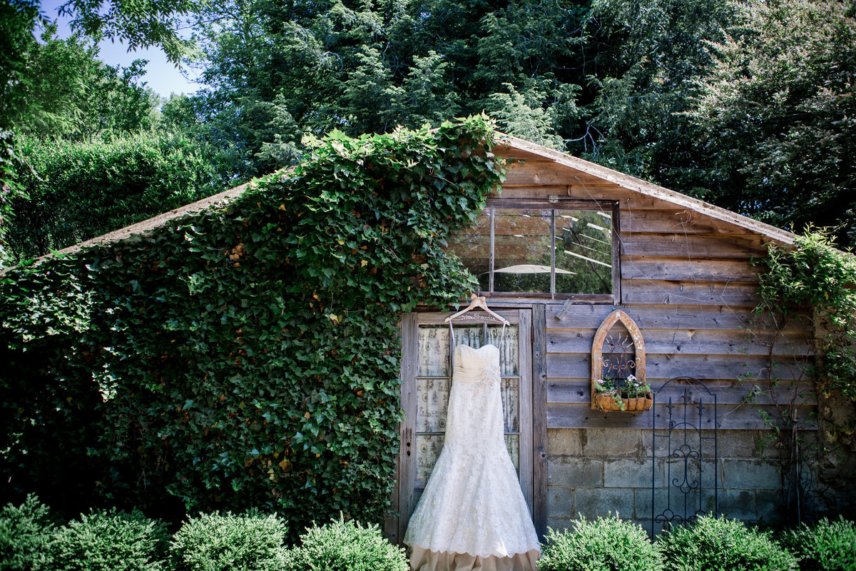 Dress hangs on a shack covered in ivy at black fox farm wedding venue by Knoxville Wedding Photographer, Amanda May Photos.