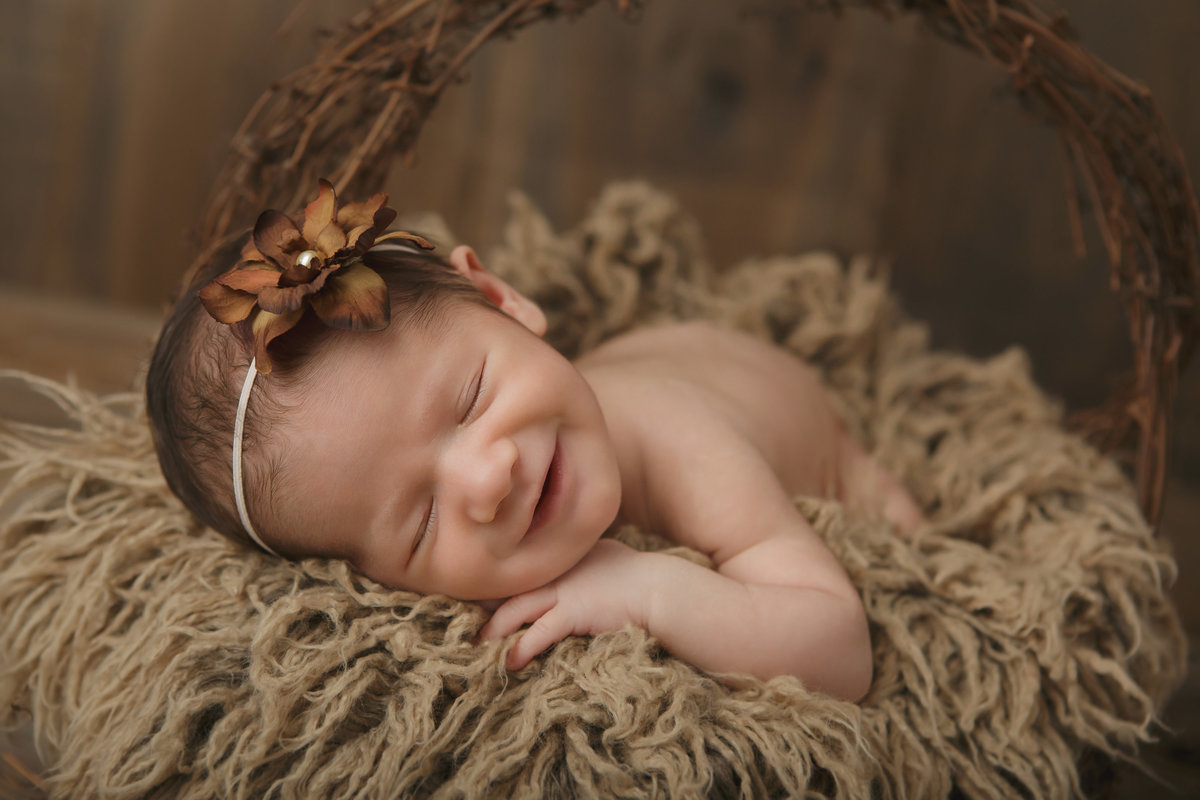 Brewster newborn baby girl smiling while sleeping in a fur lined grapevine basket with wood background by Hudson Valley professional photographer Autumn Photography Cornwall NY photo studio
