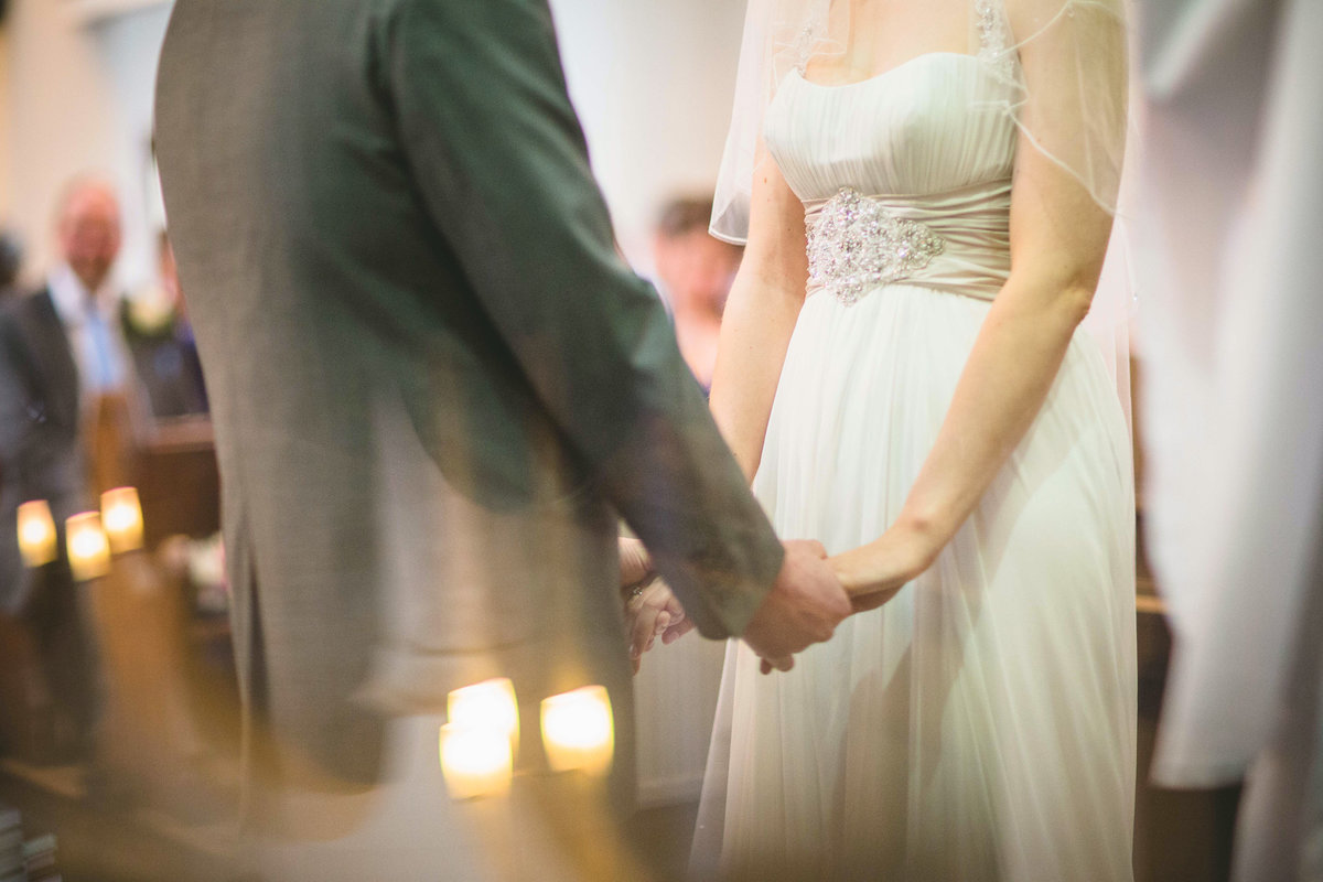 bride and groom holding hands in church wedding ceremony