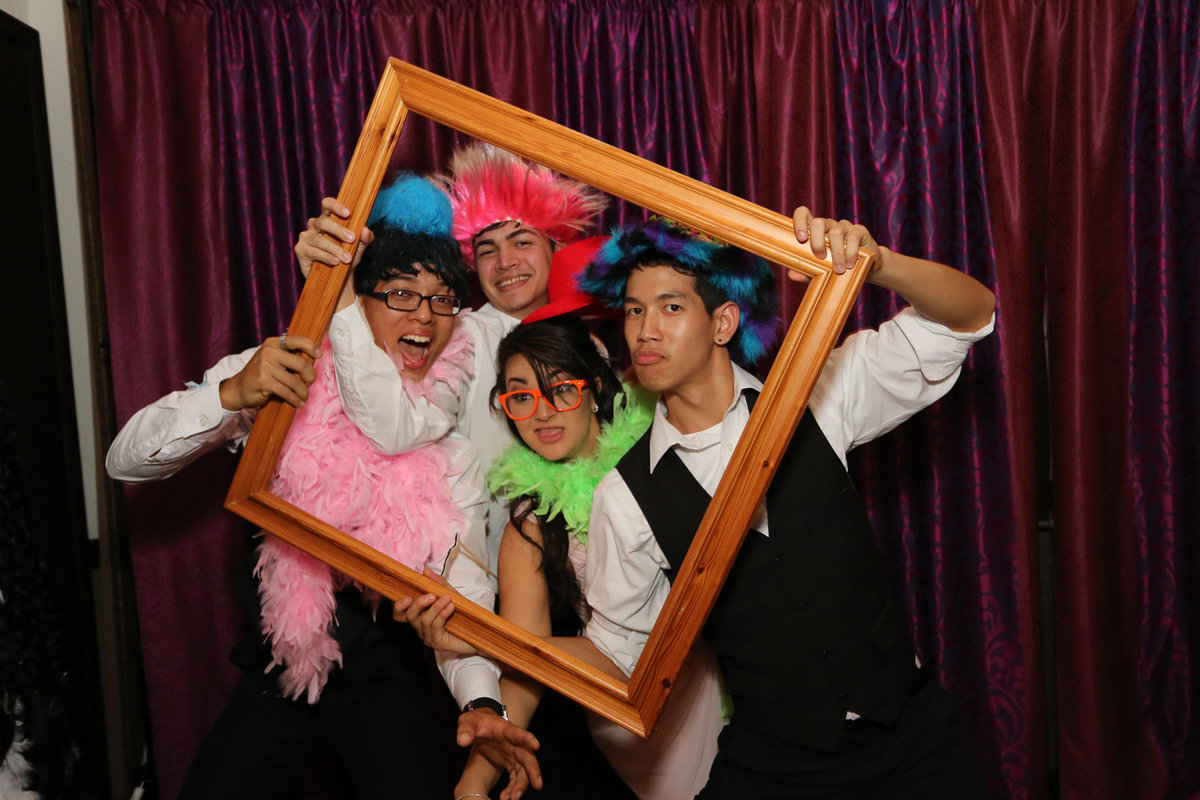 Fun loving foursome wearing hats and boas while holding a picture frame. Photobooth by Ross Photography, Trinidad, W.I..