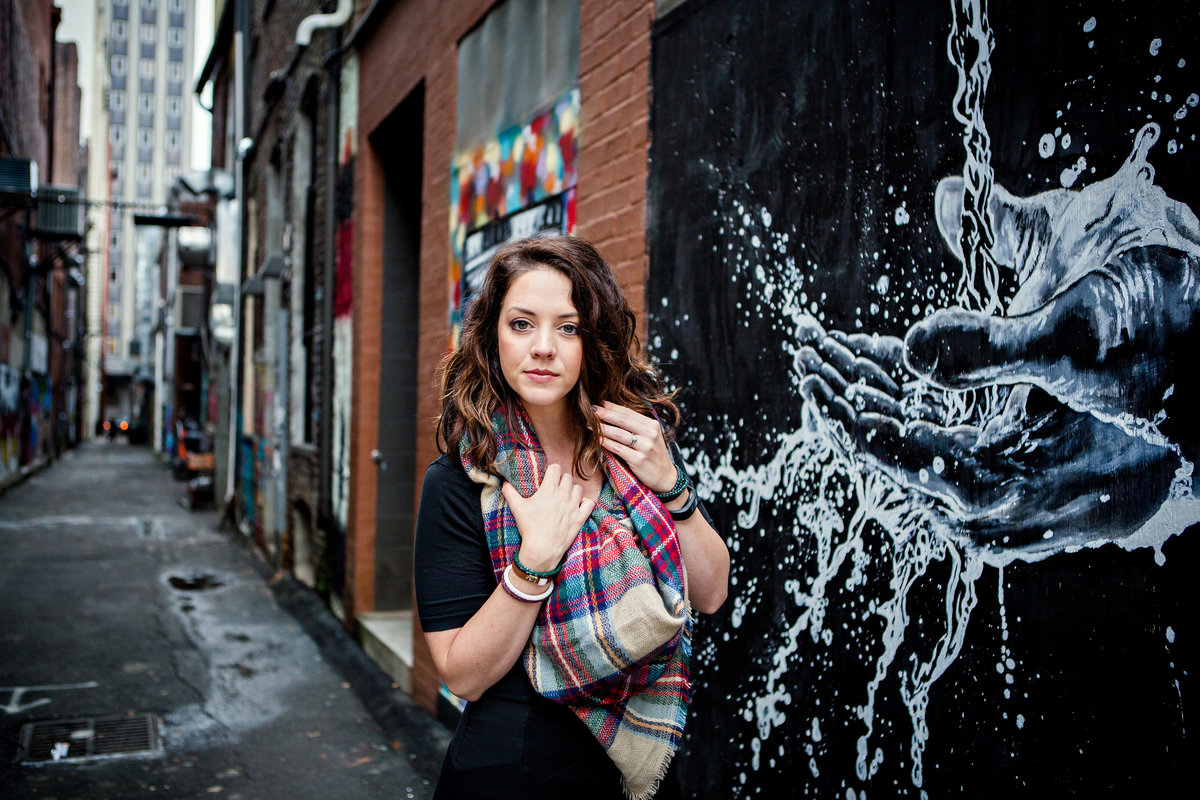Girl standing in alley by art piece of hands in water for her senior pictures by Knoxville Wedding Photographer, Amanda May Photos.