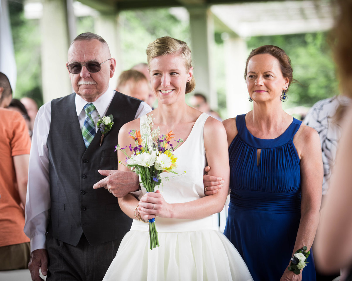 Bride processes with parents and bouquet, wedding ceremony Chicago.