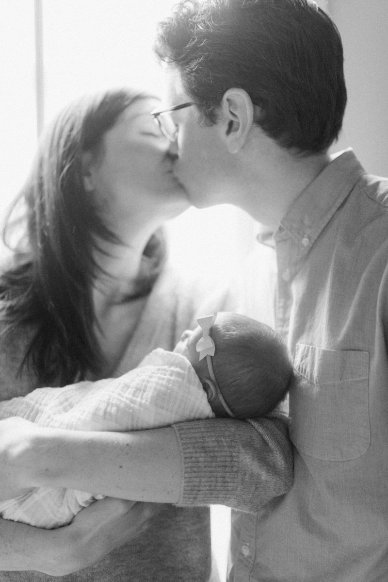 couple kissing with newborn baby
