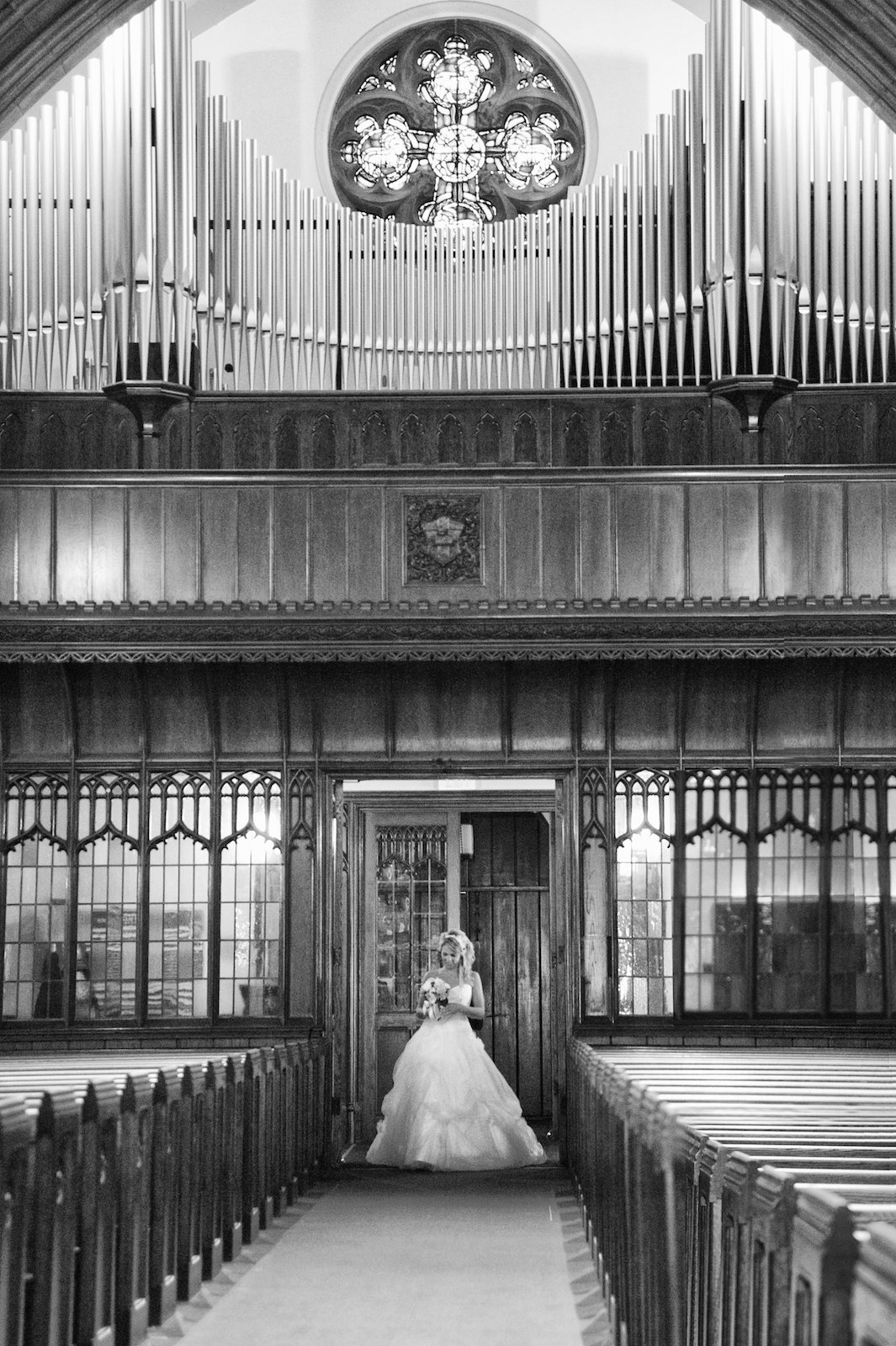 black and white wedding photo of bride walking down the aisle by herself