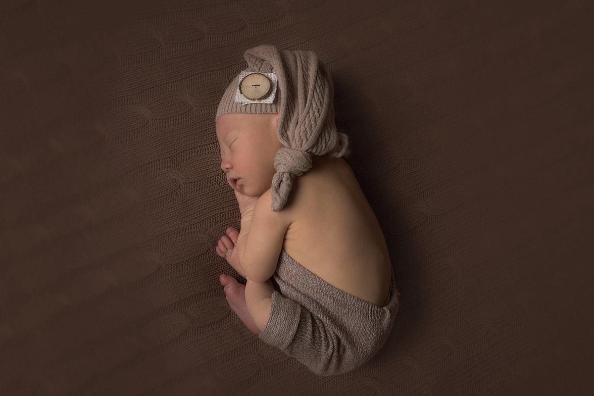 sleeping baby boy on brown blanket