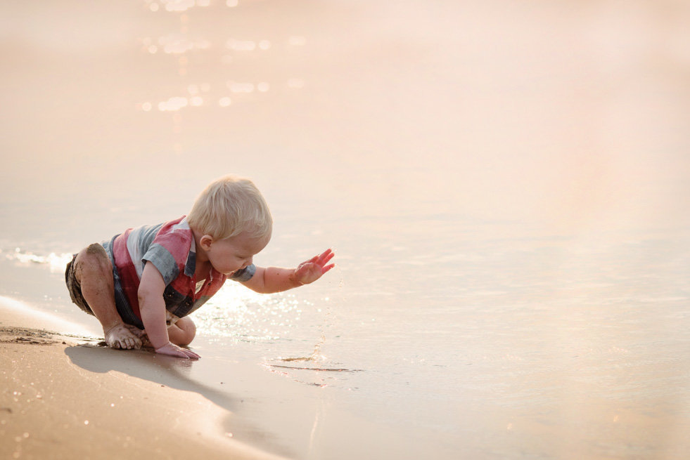 a baby boy splashes the ocean at sunrise