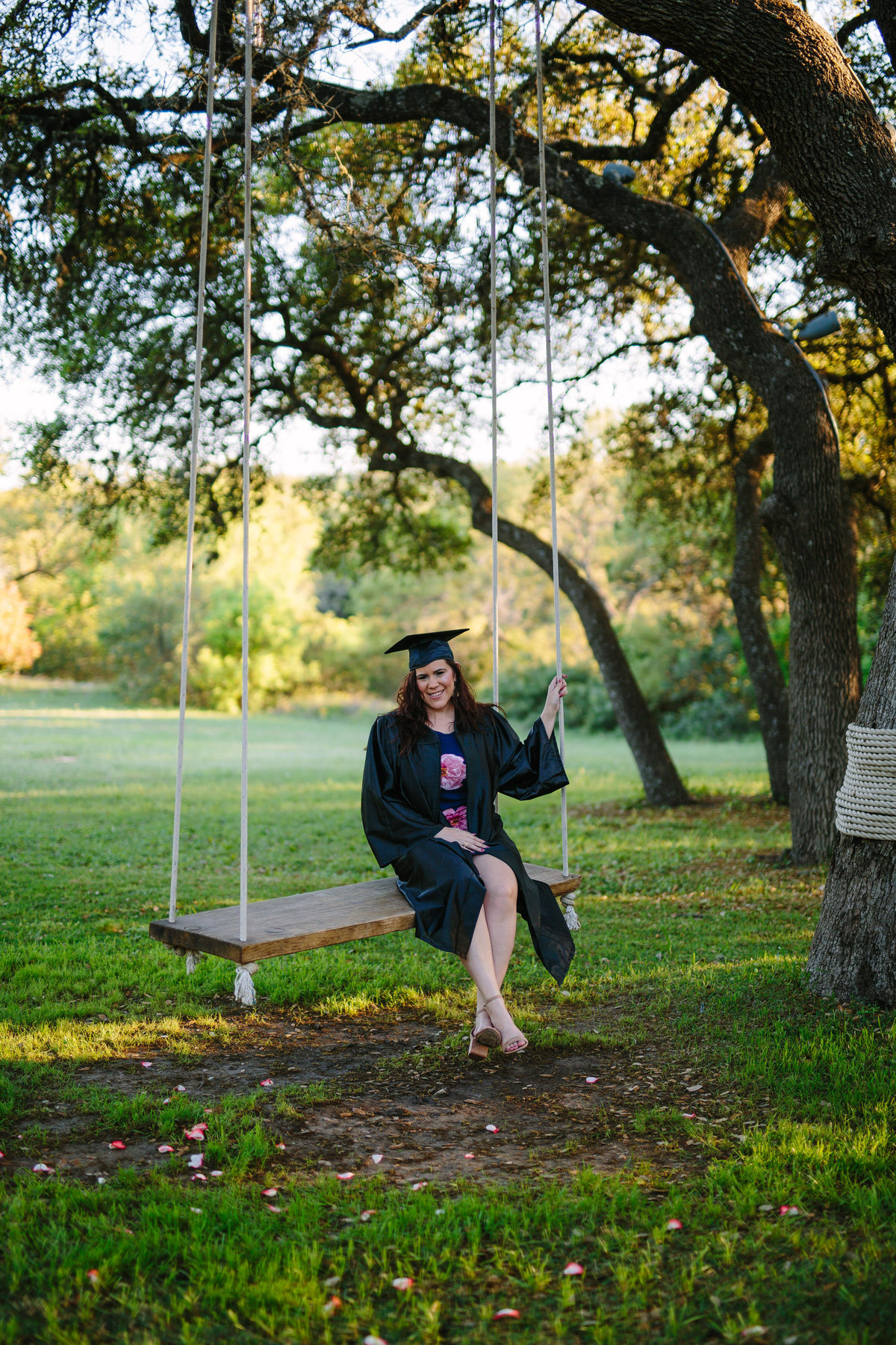 college senior session in cap and gown sitting on swing by San Antonio photographer