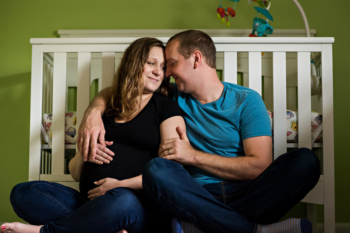 A newly pregnant couple sit against the babies crib in their home maternity session.