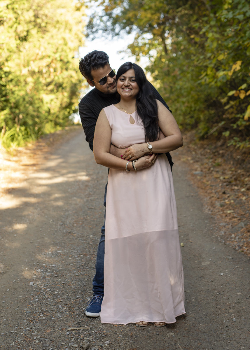 engaged indian couple standing on a dirt road slope at Forks of the Credit River with the guys arms around her waist as she smiles brightly