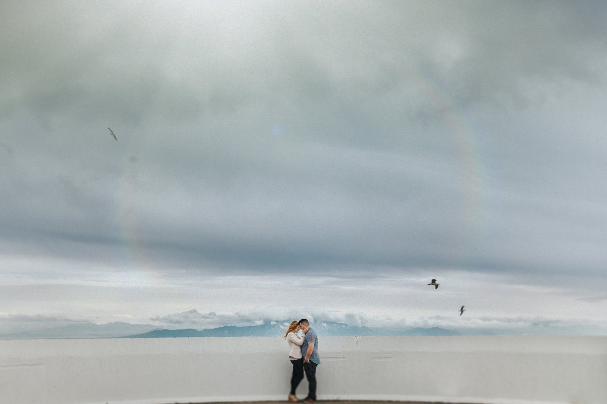 Destination Wedding Photographer Jono Symonds photographs a couple embracing on the top of The Rock in Gibraltar with stunning views of Africa in the distance