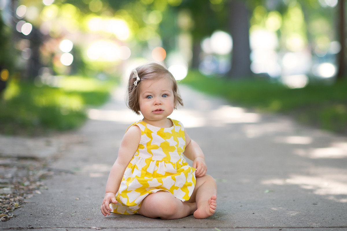 a one year old girl sits on the sidewalk