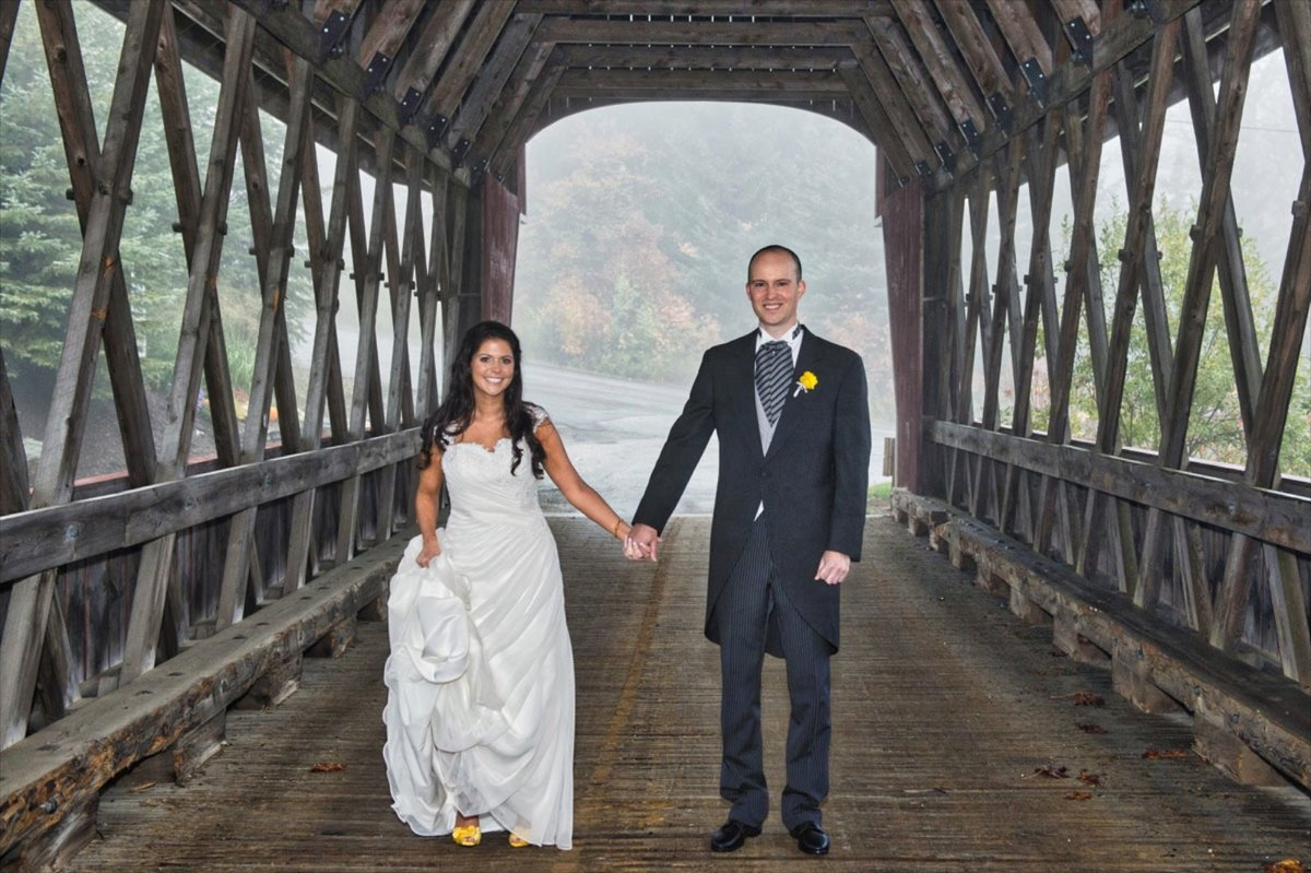 bride and groom standing underneath a covered bridge in Vermont at their Stratton Resort wedding in the fall