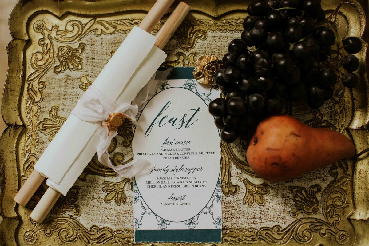 Invitation by Blu3 design sits beside fruit on a gold tray