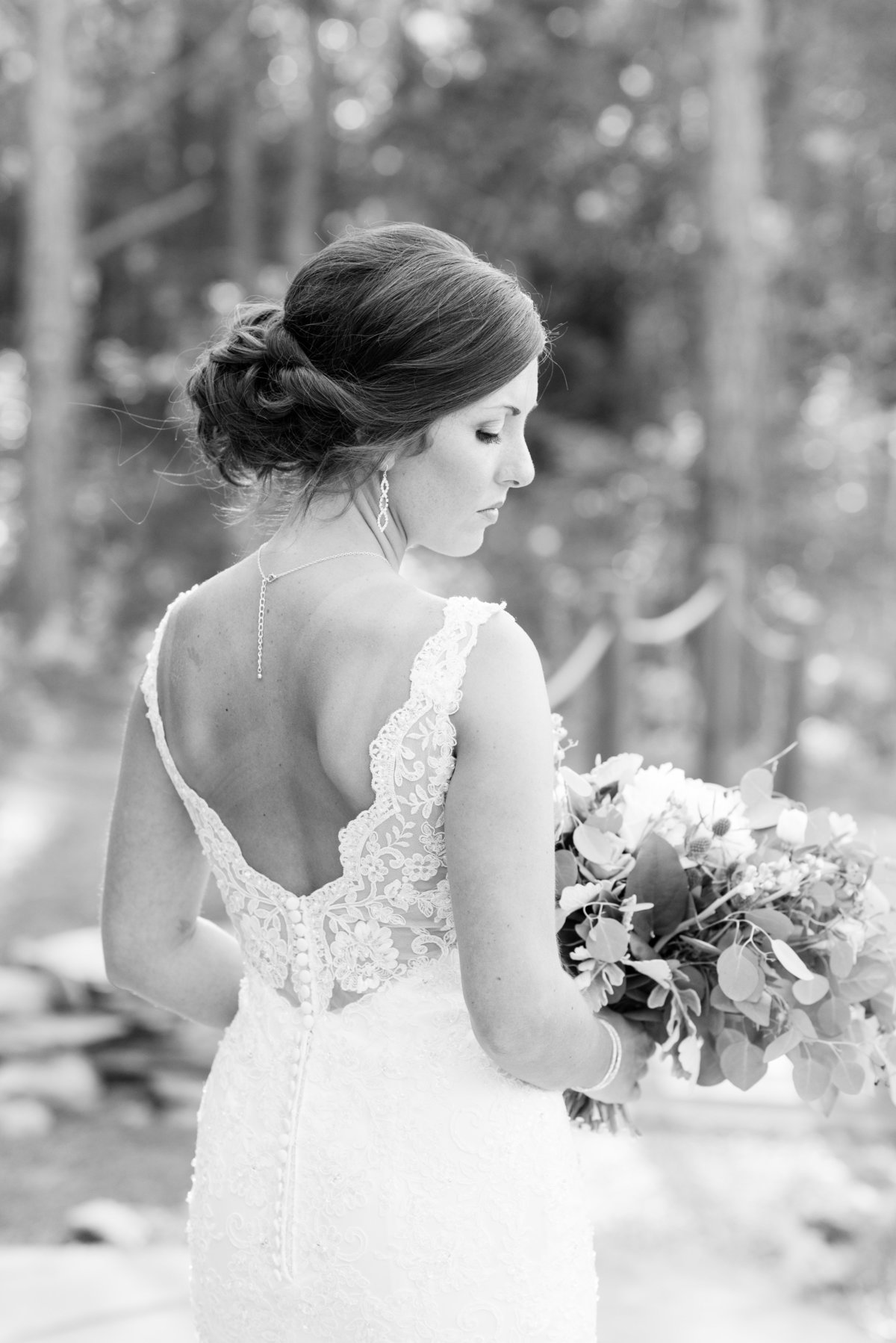 a black and white photograph of a bride wearing a laced thin strapped wedding dress looking down holding her wedding bouquet at Meadows at Walnut Cove