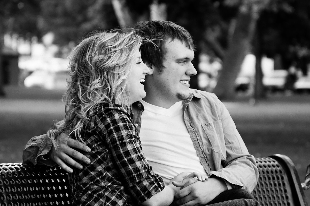 engaged couple laughing in the park