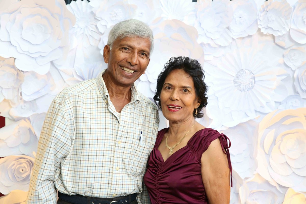 An older man and woman couple smile in front of 3d backdrop. Photobooth by Ross Photography, Trinidad, W.I..