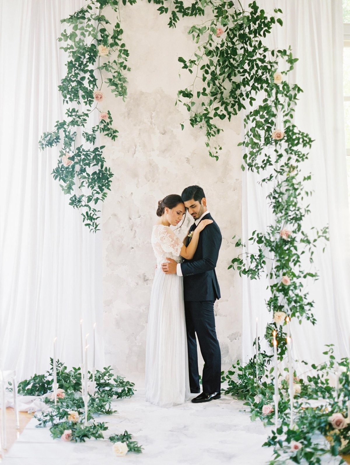 Bride and groom standing in front of custom watercolor wedding backdrop By Brittany Branson