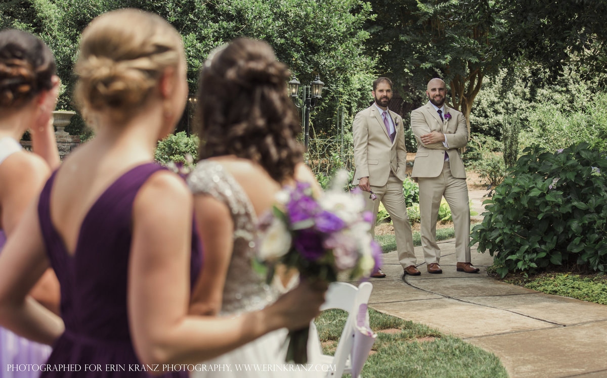 charlotte wedding photographer captures a documentary moment of groom and best man watching bride and bridesmaids from across the garden at Barclay Villa in Raleigh North Carolina