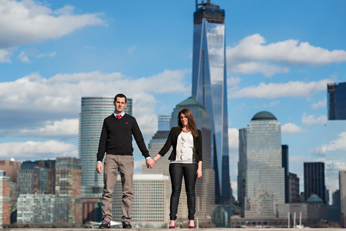 An engaged couple hold hands with the NYC skyline behind them.