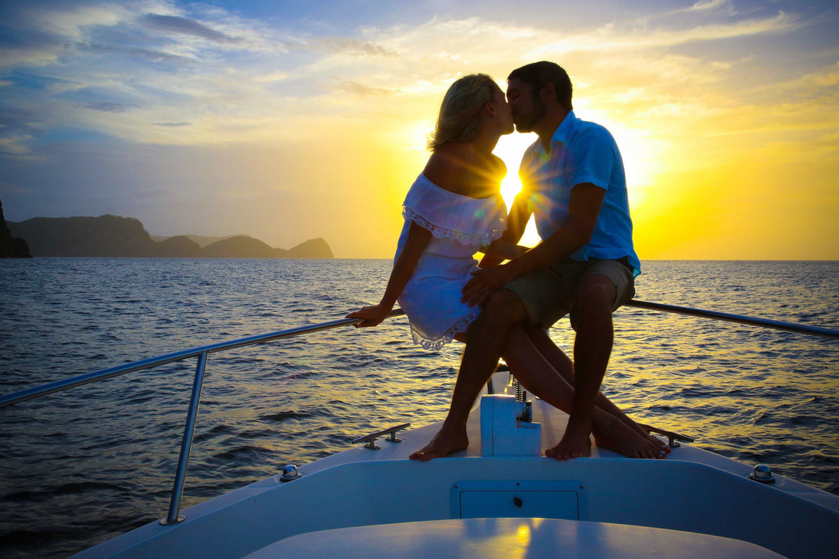 A couple kisses while sailing into the sunset on the bow of a yacht. Photo by Ross Photography, Trinidad, W.I..