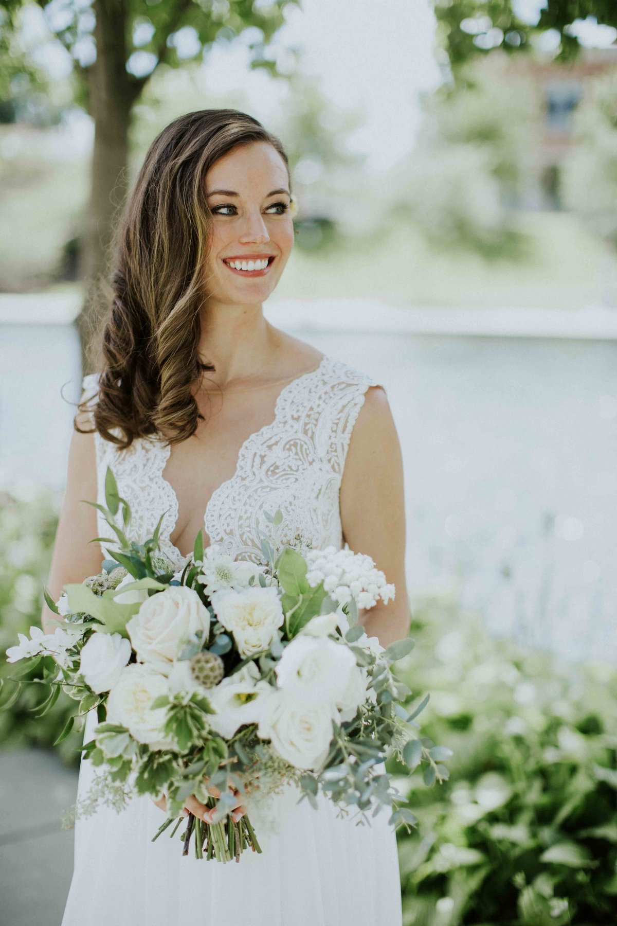 Bride smiles while holding bouquet in Indianapolis wedding