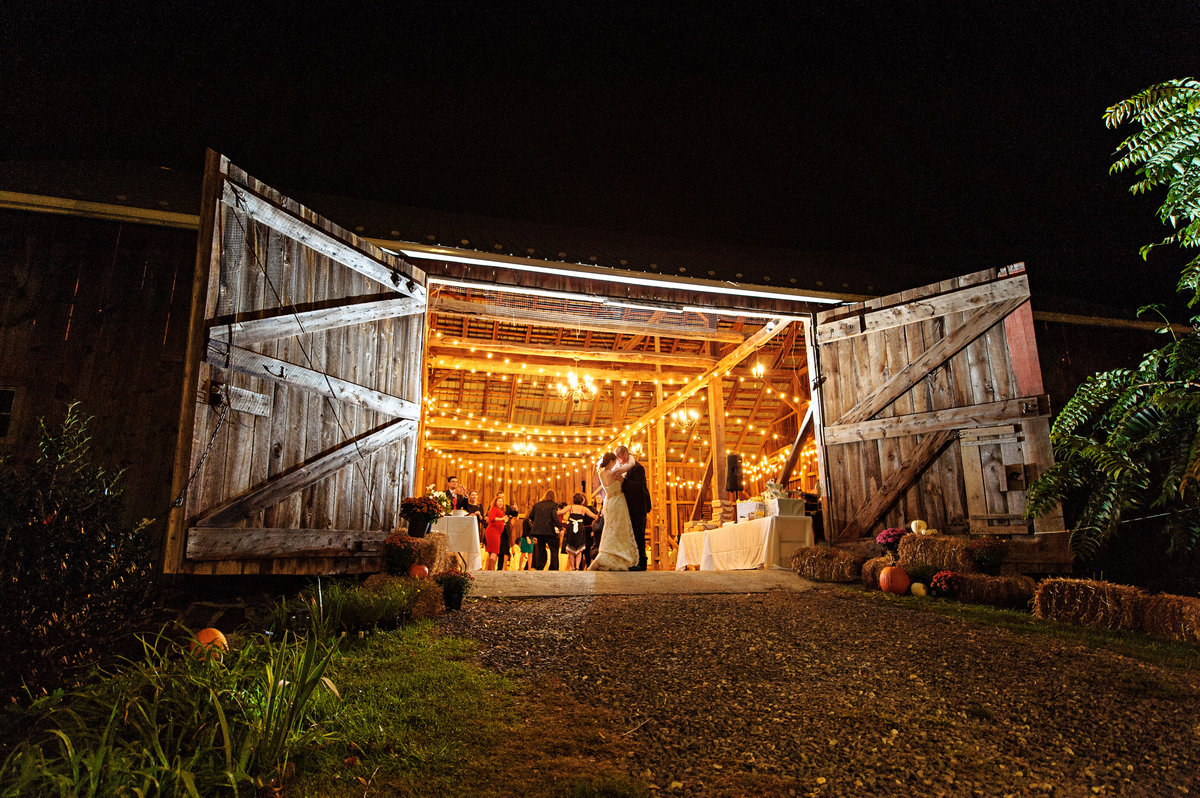 A bride and groom kiss at the entrance of their rustic barn wedding venue.