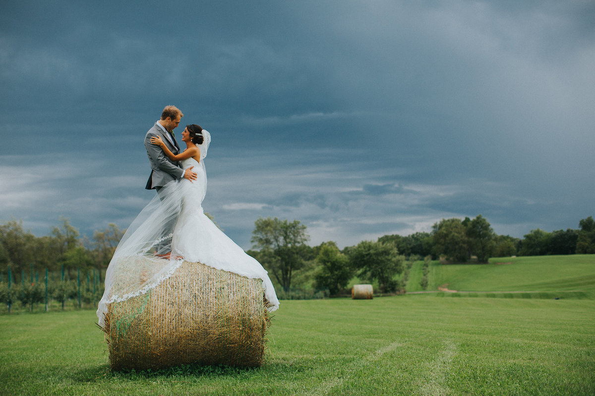 bride and groom standing on hay bale under stormy sky