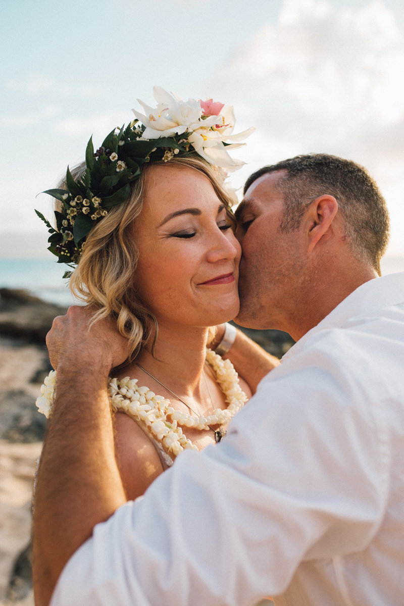 Groom giving bride a kiss as he puts pikake lei around her neck on the beach