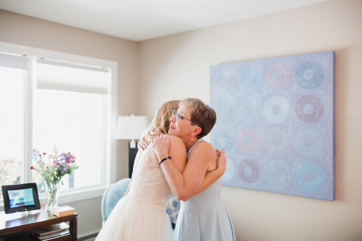 Bride hugging her mother before the wedding ceremony. Getting ready in her home.