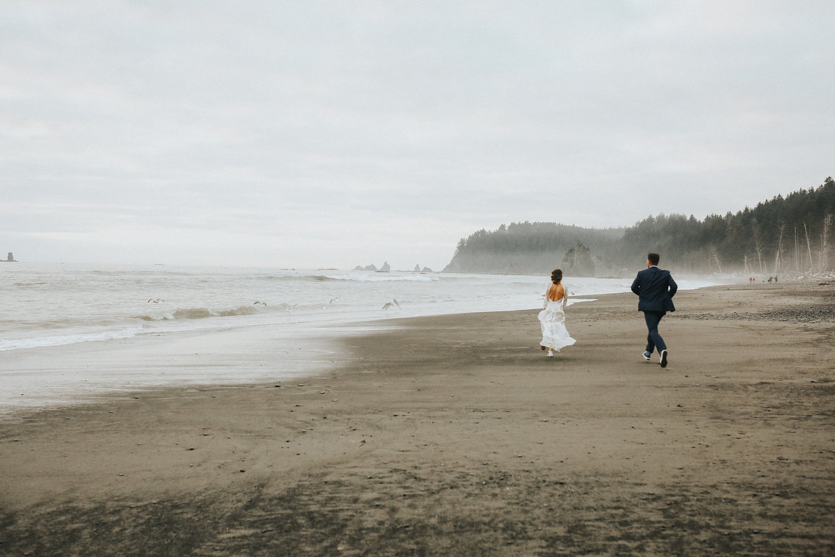 Bride and groom chase seagulls during their elopement wedding at Cannon  Beach on the Oregon Coast.