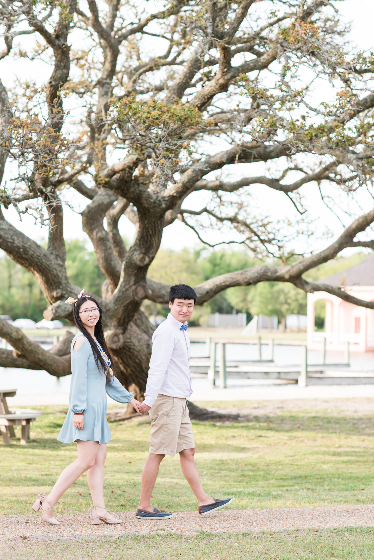 a bride wearing a short blue dress walking hand in hand with her fiance wearing khakis with a buttoned up shirt and a bowtie in front of a large magnolia tree at Whalehead Club at Corolla Beach
