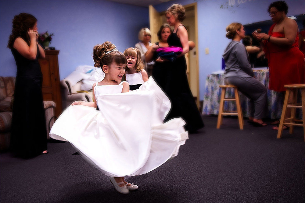 A flower girl spins and spins as the rest of the gals from the bridal party get ready at the First Christian Church in Clinton, Illinois