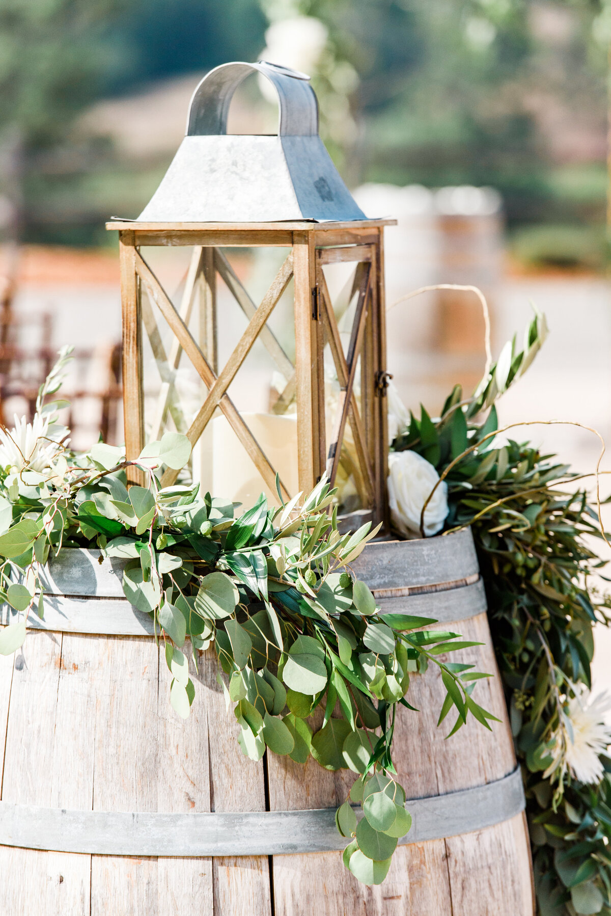 a wine barrel with a lantern and green garland