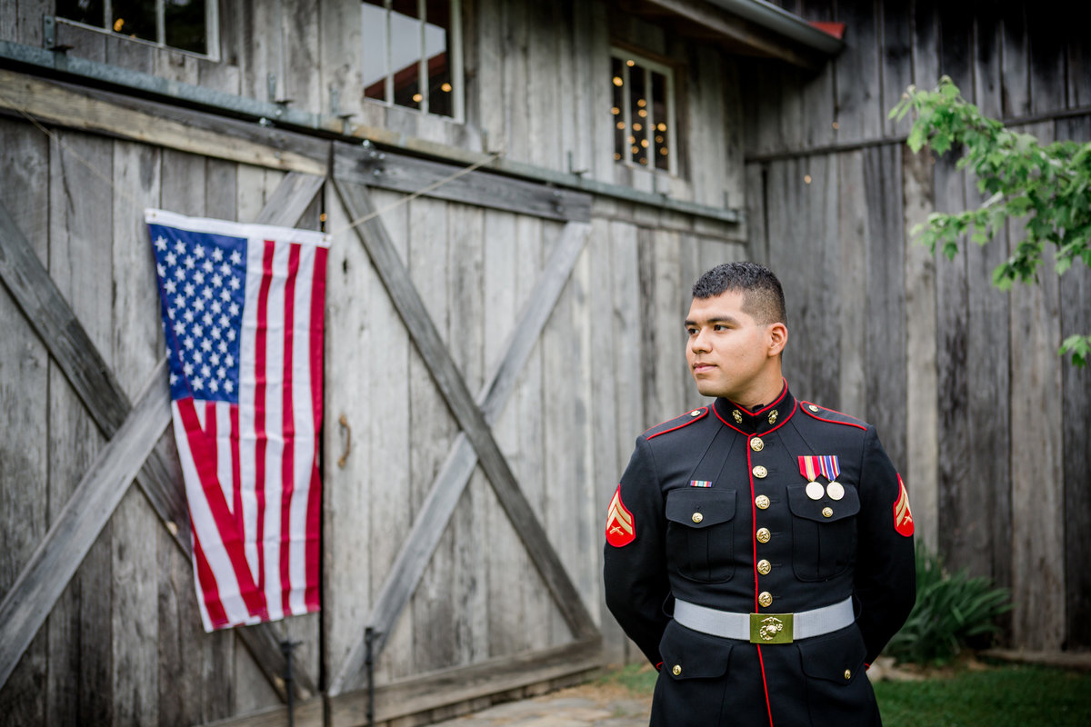 Groom in uniform standing in front of an american flag hanging on a barn at the barn at highpoint farms wedding venue by Knoxville Wedding Photographer, Amanda May Photos.