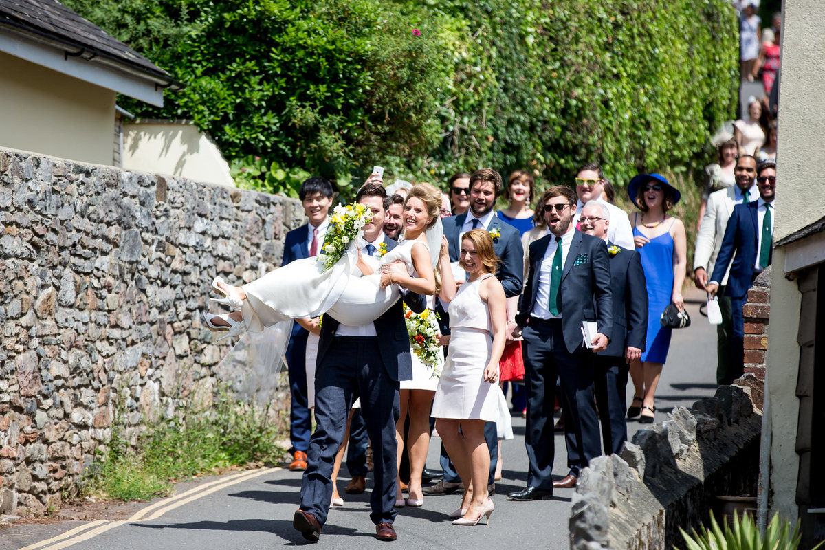 groom carrying bride at devon village wedding
