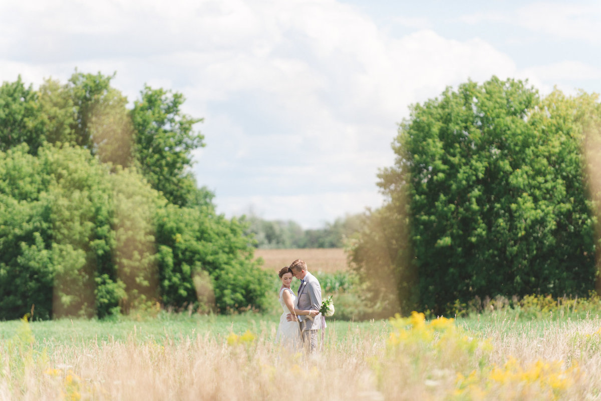 bride and groom  standing in the tall grass at strathmere in the summer