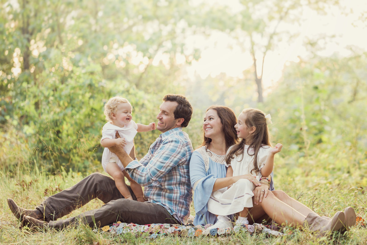 A family smiles during their summer Charlotte family photography session.