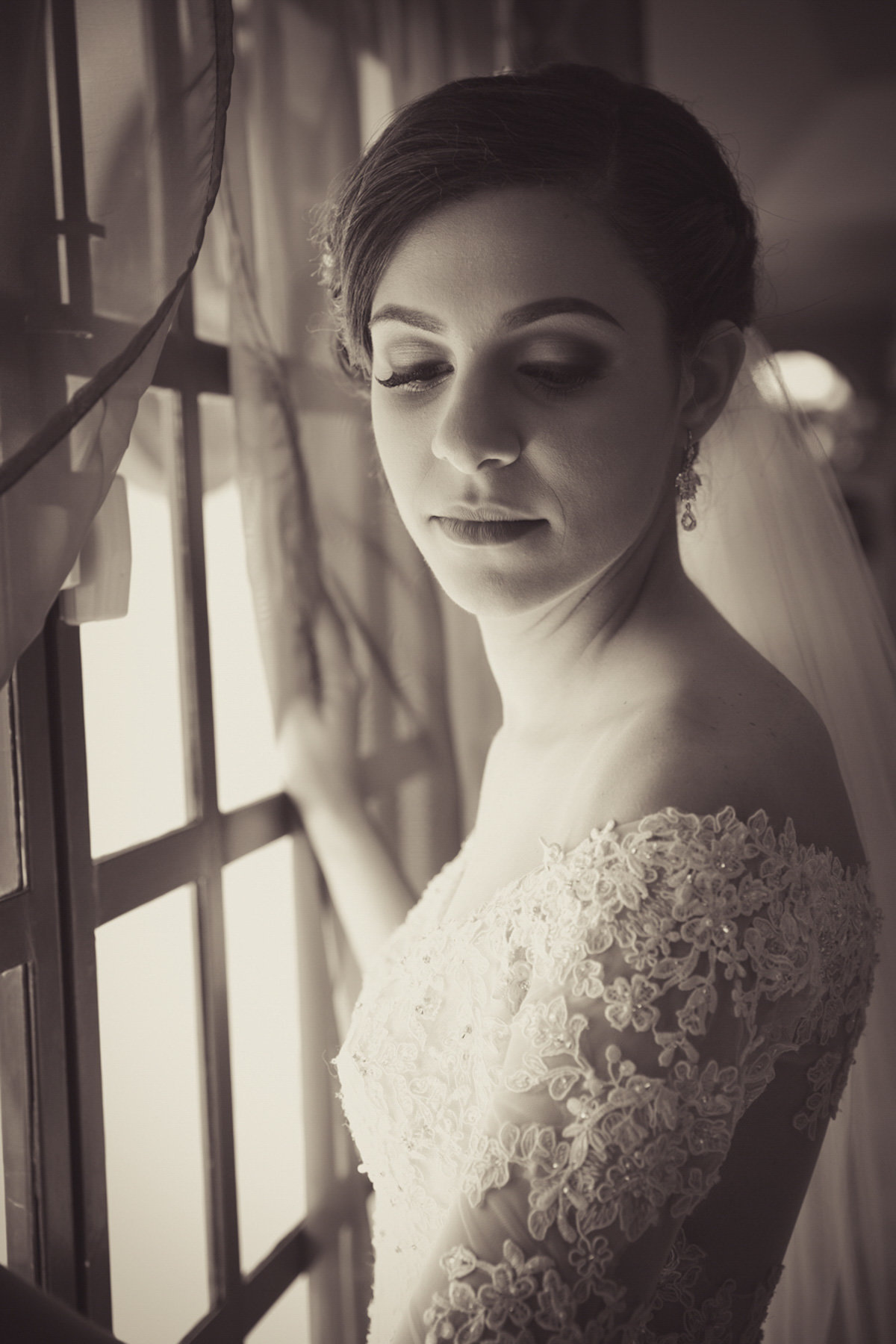 Glamour shot of bride against window in B+W. Photo by Ross Photography, Trinidad, W.I..