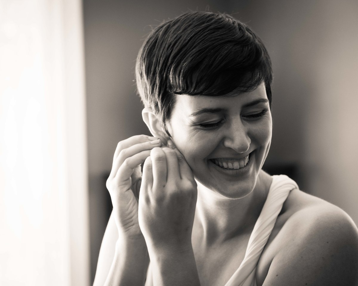 Smiling bride puts on earrings before wedding ceremony, Charlottesville VA.