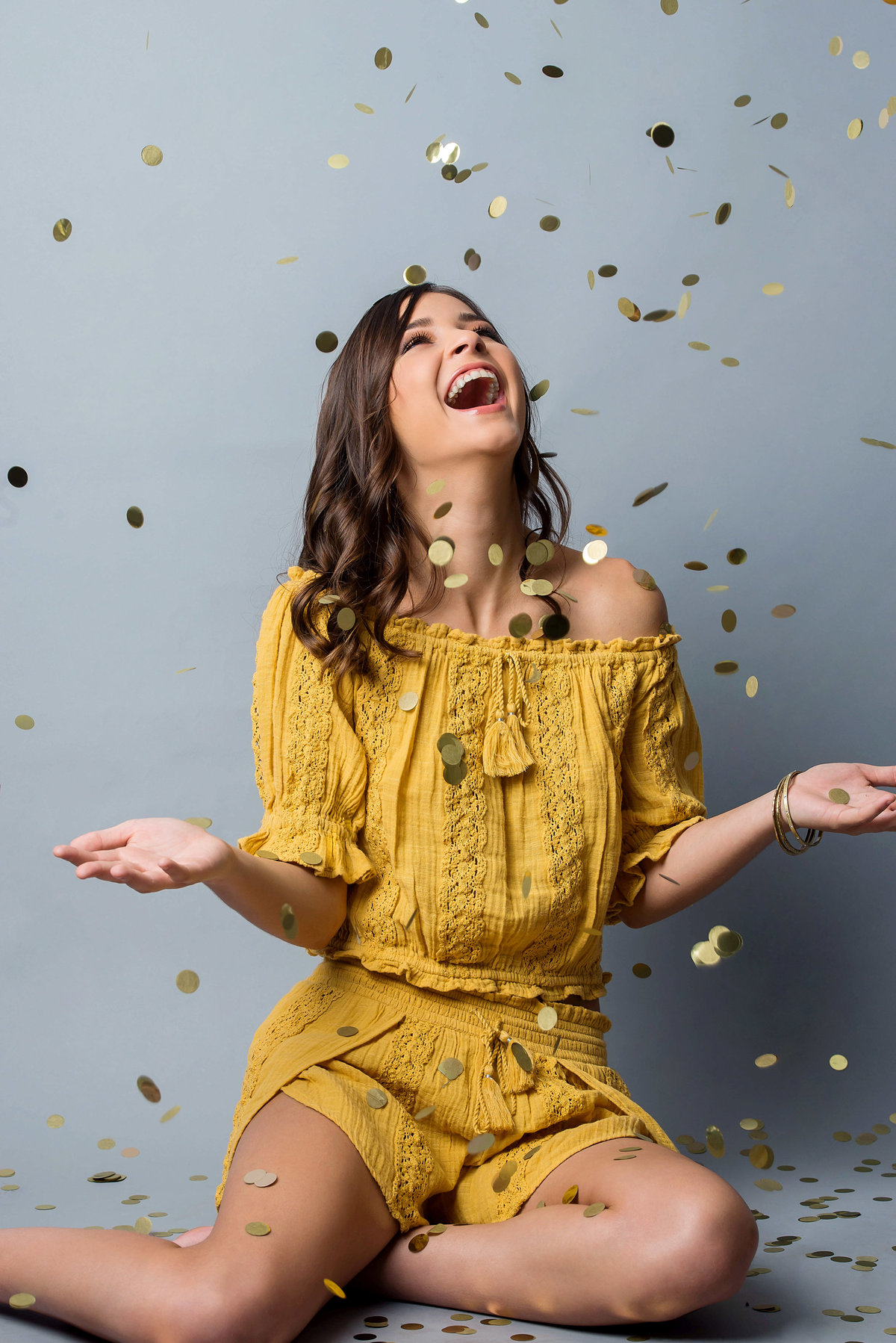 senior in studio with gold confetti