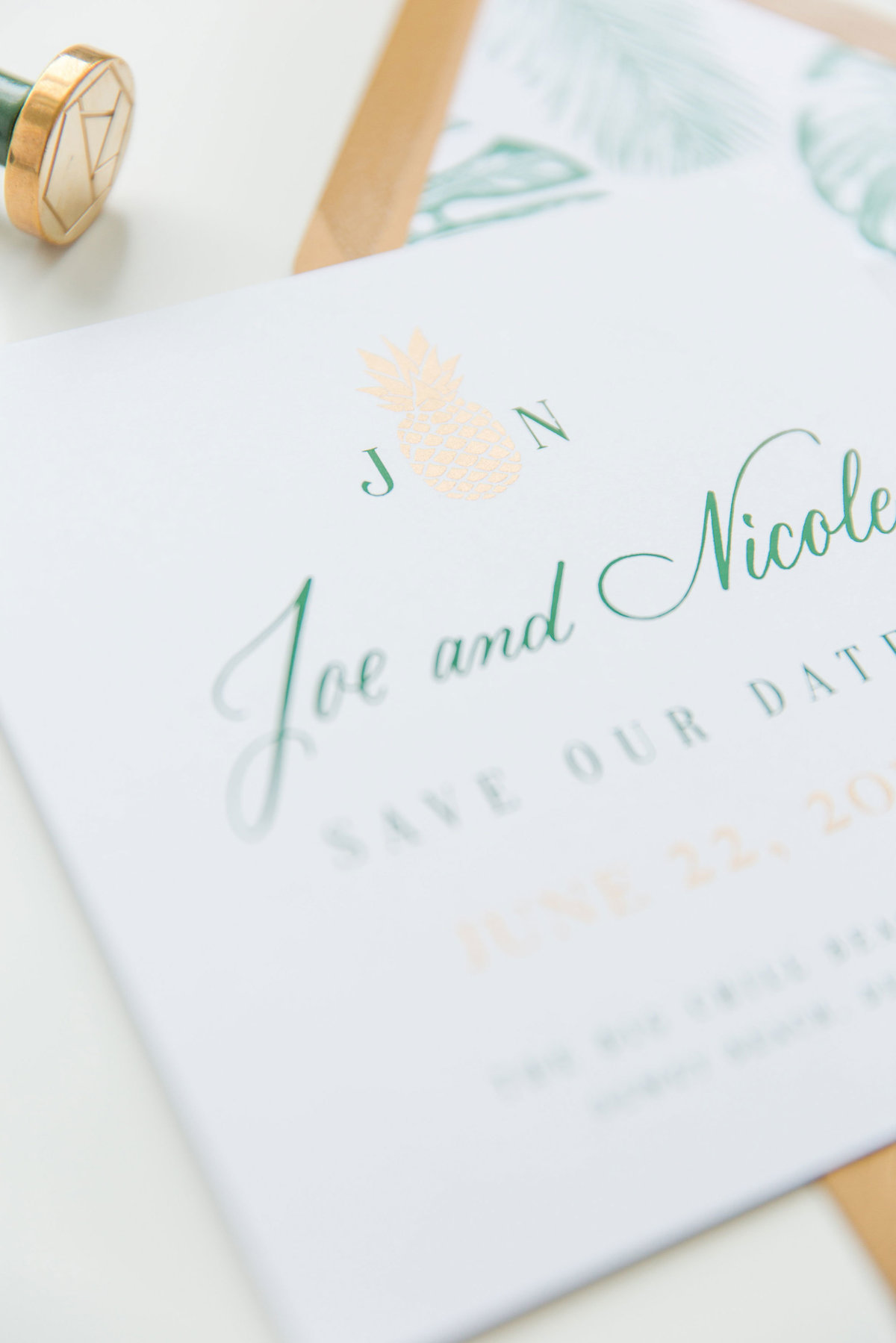 Closeup of gold ink pineapple with green calligraphy on wedding save the date by Lewes Lettering Co