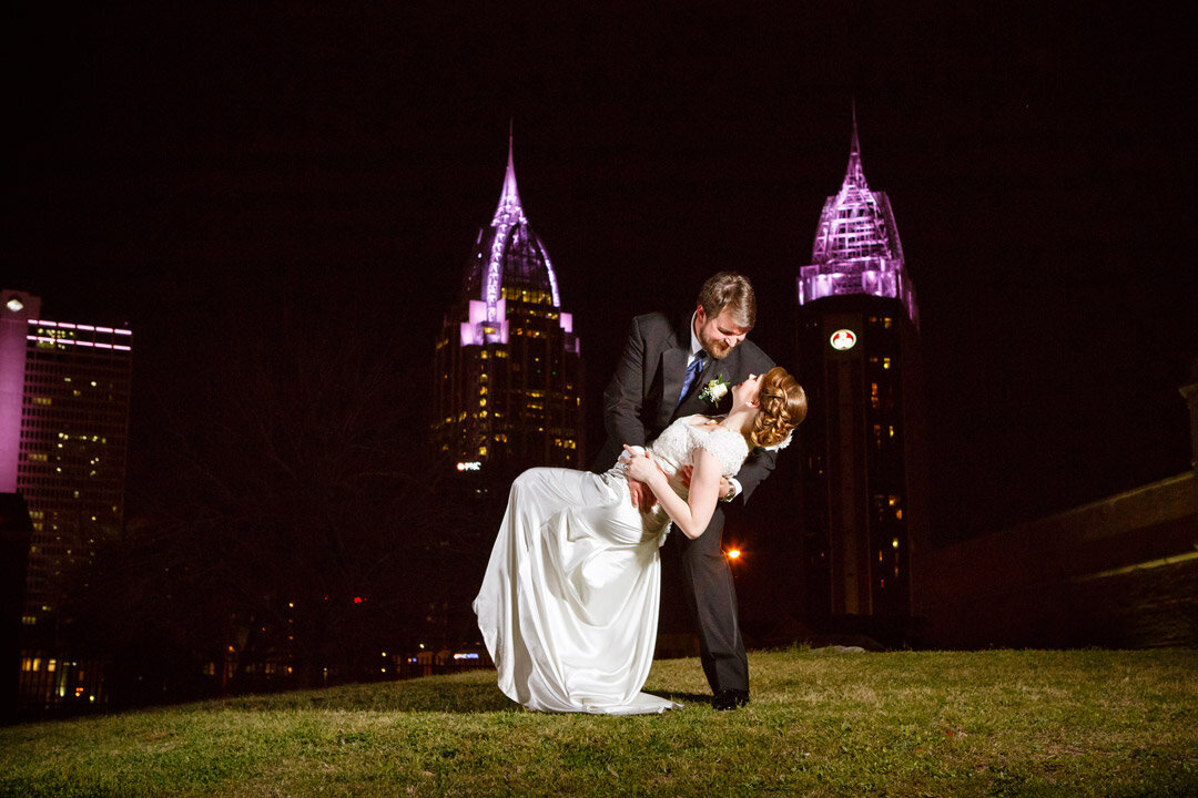 James dips his bride as they pose for photos overlooking the city of Mobile Alabama at their wedding reception at the Fort Conde Inn.