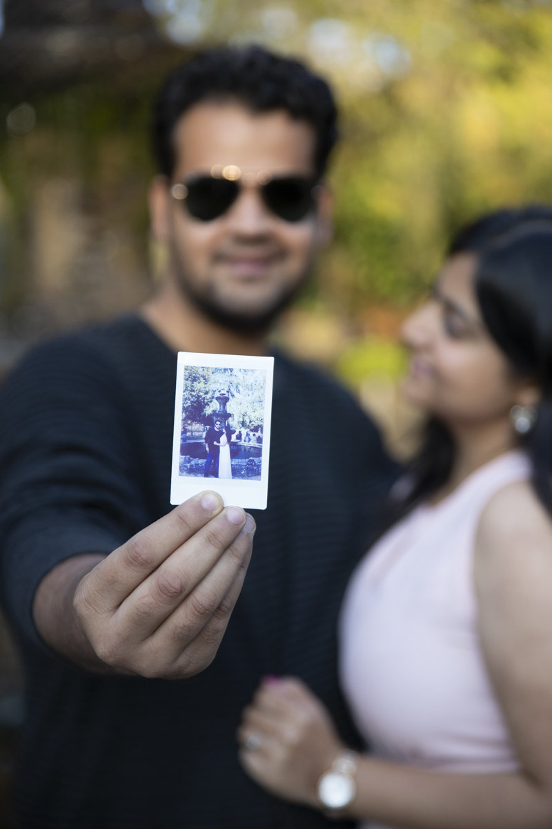 Engaged couple holding a instax instant picture which is in focus while they are blurred out in the background at the Forks of the Credit in Belfountain