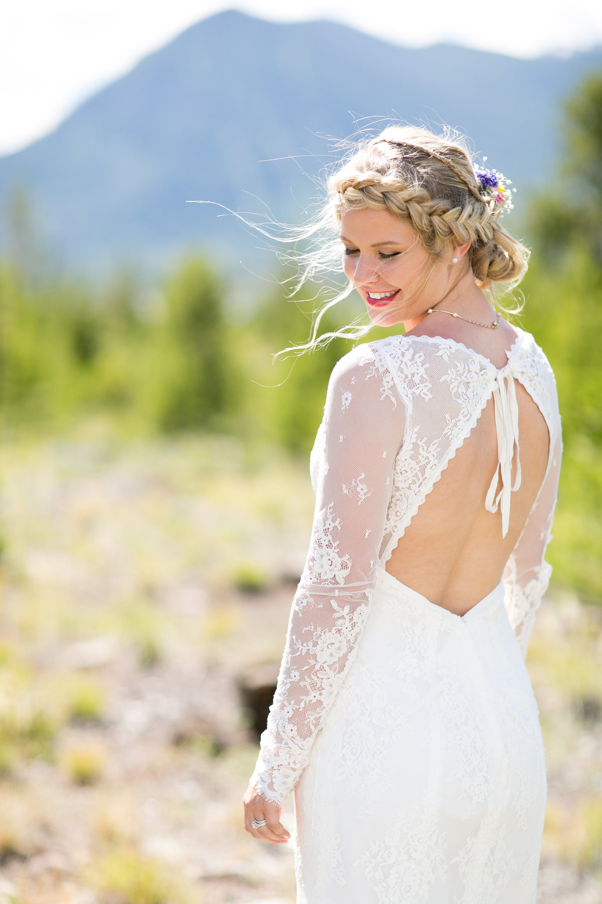Bride with backless wedding dress standing in front of a mountain
