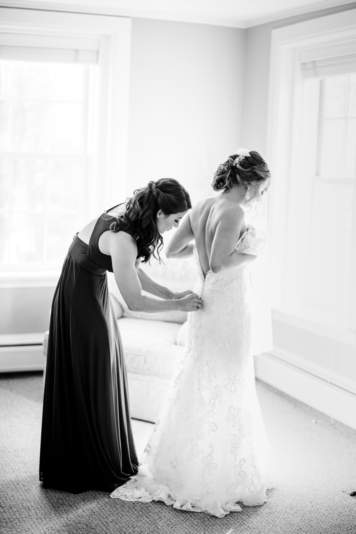 bride putting on her wedding gown black and white image