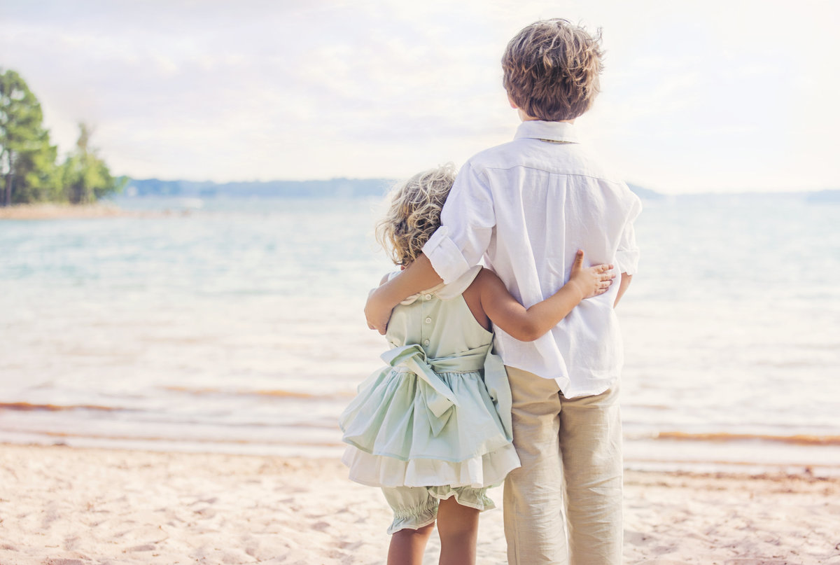 charlotte family photographer captures a portrait of siblings hugging at Jetton Park beach