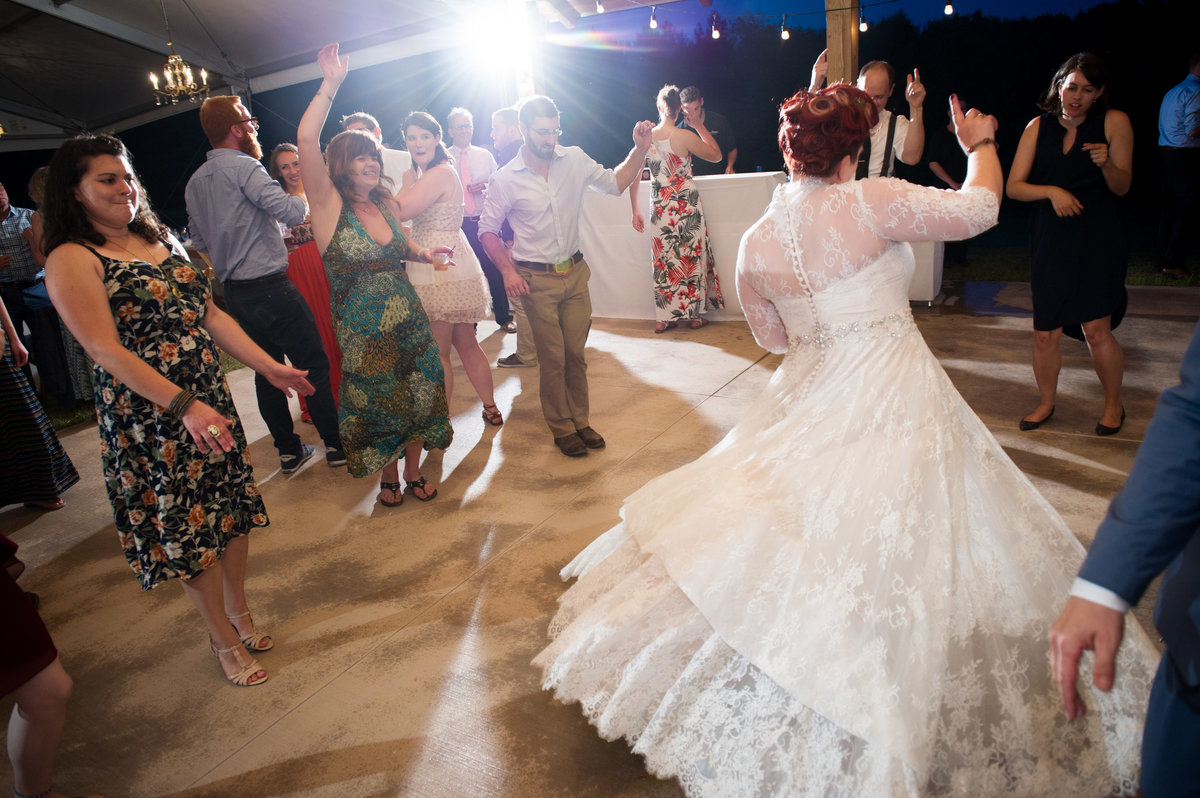 Bride dances in crowd during wedding reception, Chicago.